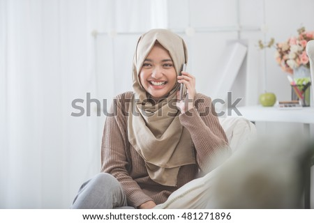 portrait of happy asian woman wearing hijab calling with mobile phone #481271896