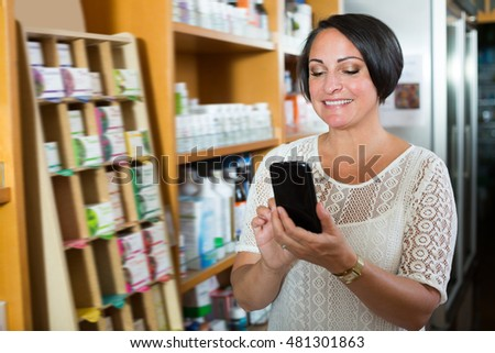 Portrait of mature woman texting using her phone in healthy food store  #481301863