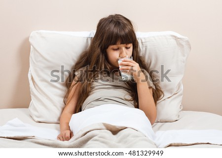 Cute little girl in pajamas is sitting on bed and drinking milk.Little girl drinking milk  #481329949