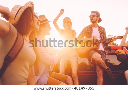 Enjoying road trip with best friends. Group of young cheerful people dancing and playing guitar while enjoying their road trip in pick-up truck together  #481497355