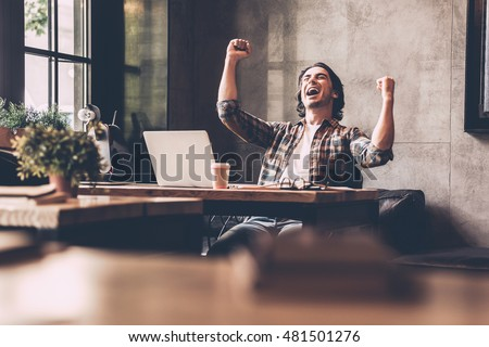 Everyday winner. Cheerful young man in casual wear keeping arms raised and looking happy while sitting at the desk in office  Royalty-Free Stock Photo #481501276