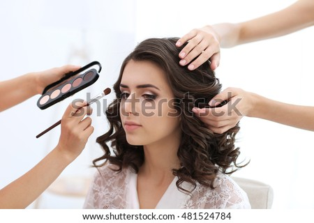 Makeup artist and hairdresser preparing bride before her wedding #481524784