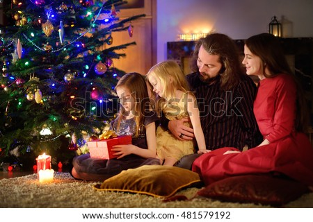 Young happy family of four unwrapping Christmas gifts by a fireplace in a cozy dark living room on Christmas eve #481579192