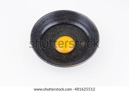 One egg yolks in black bowl on white background #481625512