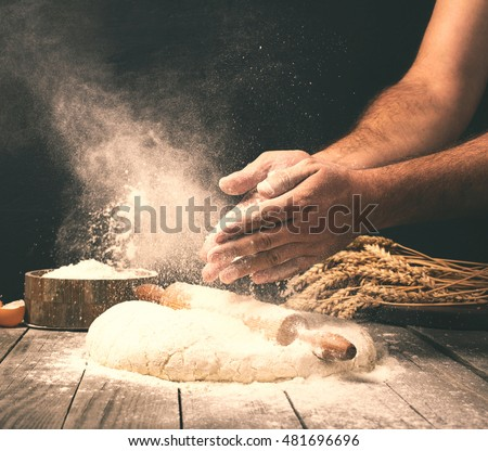 Man preparing bread dough on wooden table in a bakery close up Royalty-Free Stock Photo #481696696