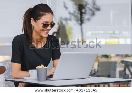 Charming woman with beautiful smile reading good news on laptop during rest in coffee shop, happy Caucasian female working in cafe. Overtime. #481711345