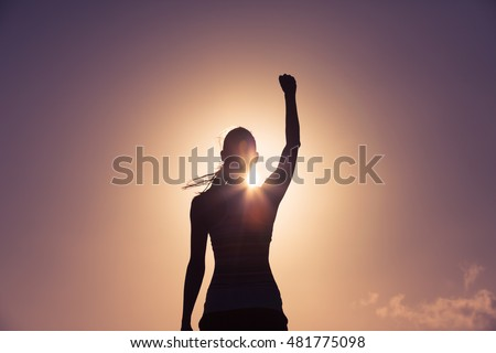 Strong confident woman with her fist up in the air.  Royalty-Free Stock Photo #481775098