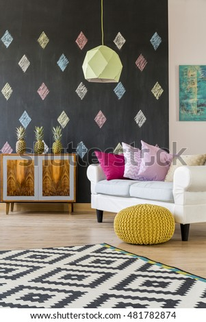 Shot of a comfortable sofa in a modern living room with a chalkboard wall covered with diamonds pattern #481782874