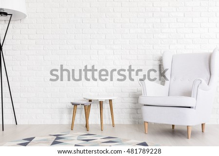 Very bright shot of white wing chair, set of coffee tables and a floor lamp next to a white brick wall #481789228