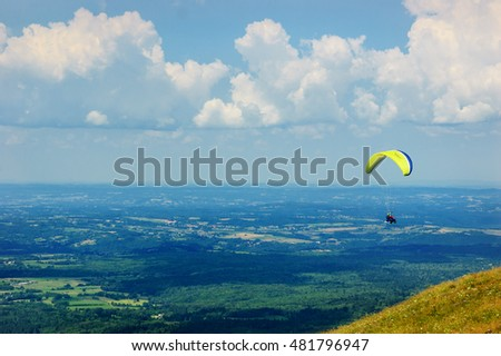 PUY-DE-DOME, FRANCE - AUGUST 16, 2016: Paragliders taking off and flying. Flying over the volcanoes is popular recreational activity in Auvergne. #481796947