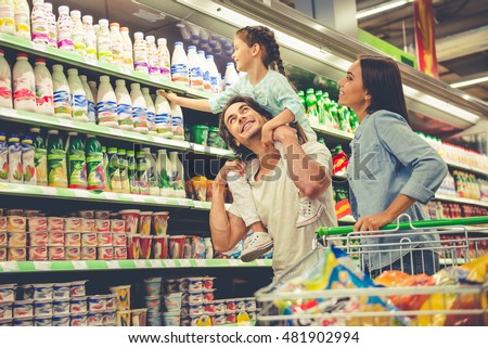 Beautiful young parents and their cute little daughter are smiling while choosing food in the supermarket. Girl is sitting on her dad's shoulders Royalty-Free Stock Photo #481902994