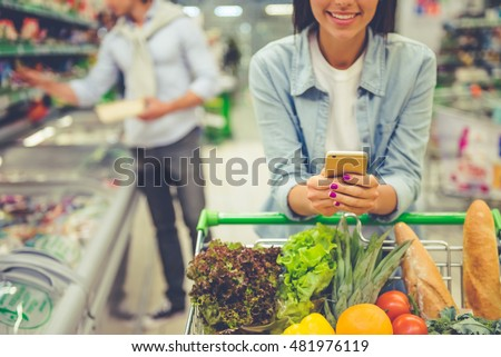 Couple in the supermarket. Cropped image of girl leaning on shopping cart, using a mobile phone and smiling, in the background her boyfriend is choosing food Royalty-Free Stock Photo #481976119