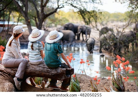 Family of mother and kids on African safari vacation enjoying wildlife viewing at watering hole #482050255