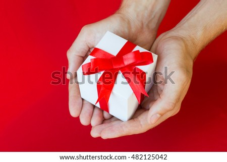 The man hands holding white gift box with red ribbon on red background #482125042