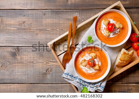 Tomato soup with cream and croutons and parsley leaves in white bowls on a napkin on a wooden table. #482168302