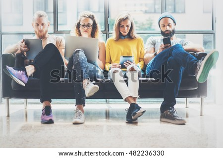 Group Adult Hipsters Friends Sitting Sofa Using Modern Gadgets.Business Startup Friendship Teamwork Concept.Creative People Working Together Marketing Project.Coworking Process Office Studio.Blurred Royalty-Free Stock Photo #482236330