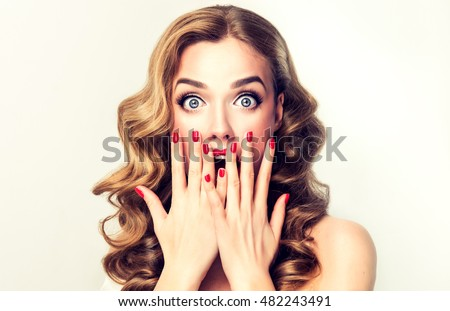 Woman surprise showing product .Beautiful girl  with curly hair  pointing to the side . Presenting your product. Isolated on white background. Expressive facial expressions Royalty-Free Stock Photo #482243491