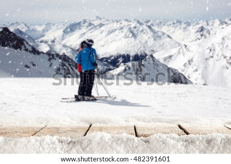 wooden table full of snow flakes and landscape of Alps with skier  #482391601