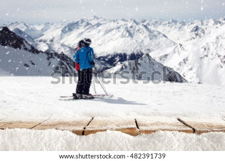 wooden table full of snow flakes and landscape of Alps with skier  #482391739