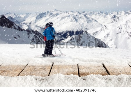 wooden table full of snow flakes and landscape of Alps with skier  #482391748