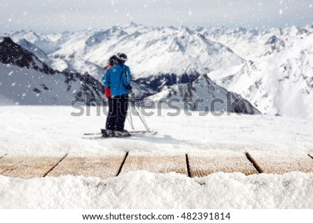 wooden table full of snow flakes and landscape of Alps with skier  #482391814