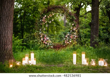 Wedding decor with flowers and candles. This is round arch of foliage and flowers.
