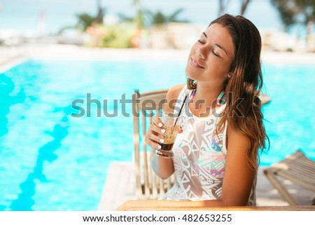 Beautiful girl drinking coffee and relaxing next to the pool. #482653255