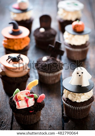 Funny cup cakes as Halloween decoration on the wooden background,selective focus  #482790064