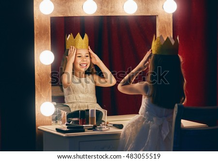 Cute little actress. Child girl in Princess costume on the background of theatrical scenes and mirrors. Royalty-Free Stock Photo #483055519