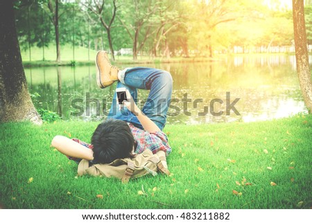 Hipster Man Relaxing on the Grass and using smart phone  #483211882