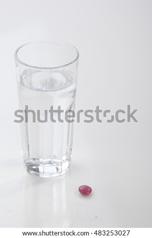 Glass of water and pills isolated on white #483253027