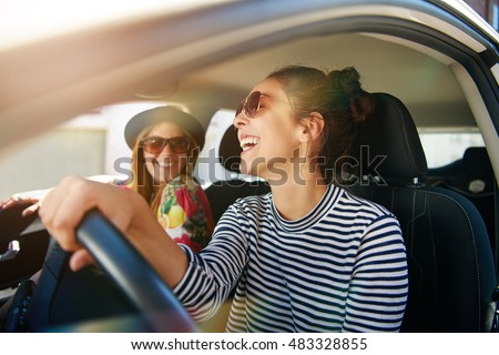 Smiling happy young woman giving her friend a lift in her car in town, profile view through the open side window with sun flare Royalty-Free Stock Photo #483328855