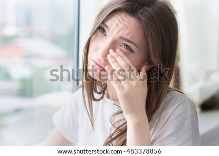 Young sad woman sits alone front of the window. Crying girl. Allergy, illness, depression, stress concept. #483378856