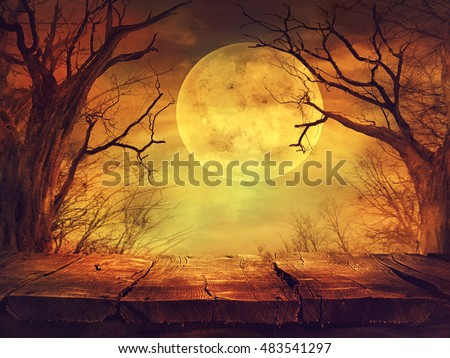 Halloween background. Spooky forest with full moon and wooden table Royalty-Free Stock Photo #483541297