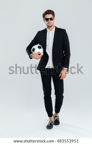 Full length portrait of a confident handsome man in sunglasses and black suit holding soccer ball over grey background #483553951