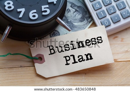 Business Plan Word on tag with clock,dollar note and calculator,Finance Concept #483650848