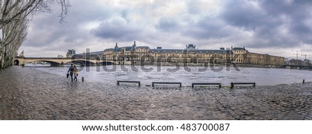The Seine River and its shore on a rainy day - The river Seine, a walk path on one shore and historical french buildings on the other one. Picture taken in Paris, France.