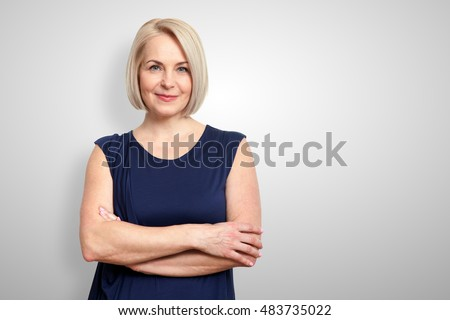 Attractive middle aged woman with folded arms on grey background Royalty-Free Stock Photo #483735022