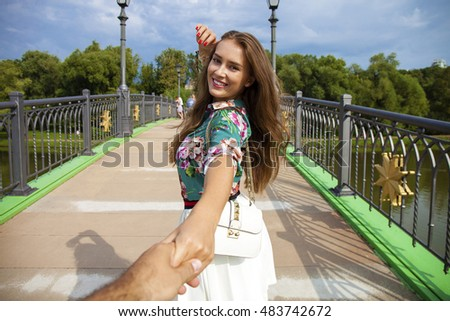 Follow me, Young beautiful woman pulls the arm of her boyfriend in a city park #483742672