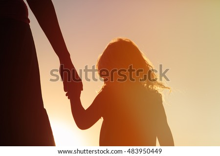 silhouette of mother and daughter holding hands at sunset Royalty-Free Stock Photo #483950449