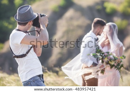 a wedding photographer takes pictures of the bride and groom in nature, the photographer in action Royalty-Free Stock Photo #483957421