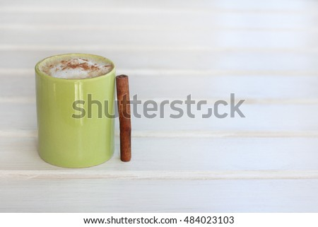 frothy cappuccino with cinnamon in a green mug on a light wooden background / aromatic coffee break #484023103