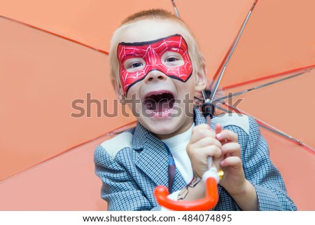 Excited caucasian boy with a spiderman mask on his face smiles at camera while holding an umbrella.
