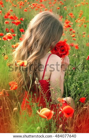 Back view of a young woman with a long blonde hair in a red dress sitting in the poppy field. Beautiful woman dreaming about something, enjoying the scent of flowers in a warm summer day. Rear view.  #484077640