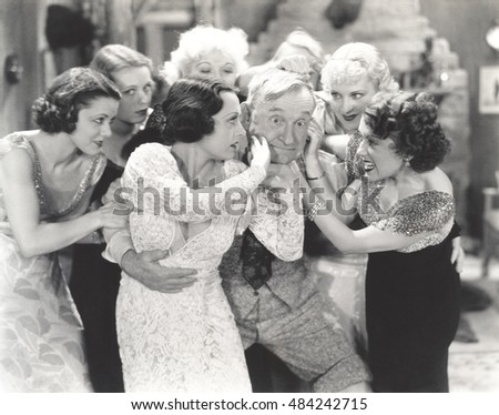 Elderly man surrounded by flirtatous young women #484242715