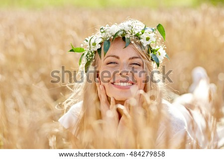 nature, summer holidays, vacation and people concept - face of happy smiling woman or teenage girl n in wreath of flowers on cereal field #484279858