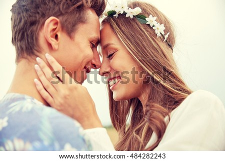 summer holidays, love, romance and people concept - happy smiling young hippie couple hugging outdoors #484282243