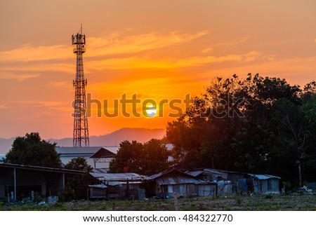 slum of labours be hide phone antenna post. slum was builded by old sink and the used material even like this slum still look nice in sunset time. #484322770