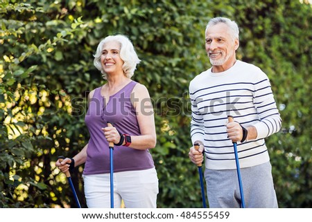 View of senior couple walking down in park with tracking sticks #484555459