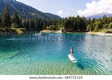 Girl on a paddleboard on the Caumasee in Flims, Switzerland #484731124